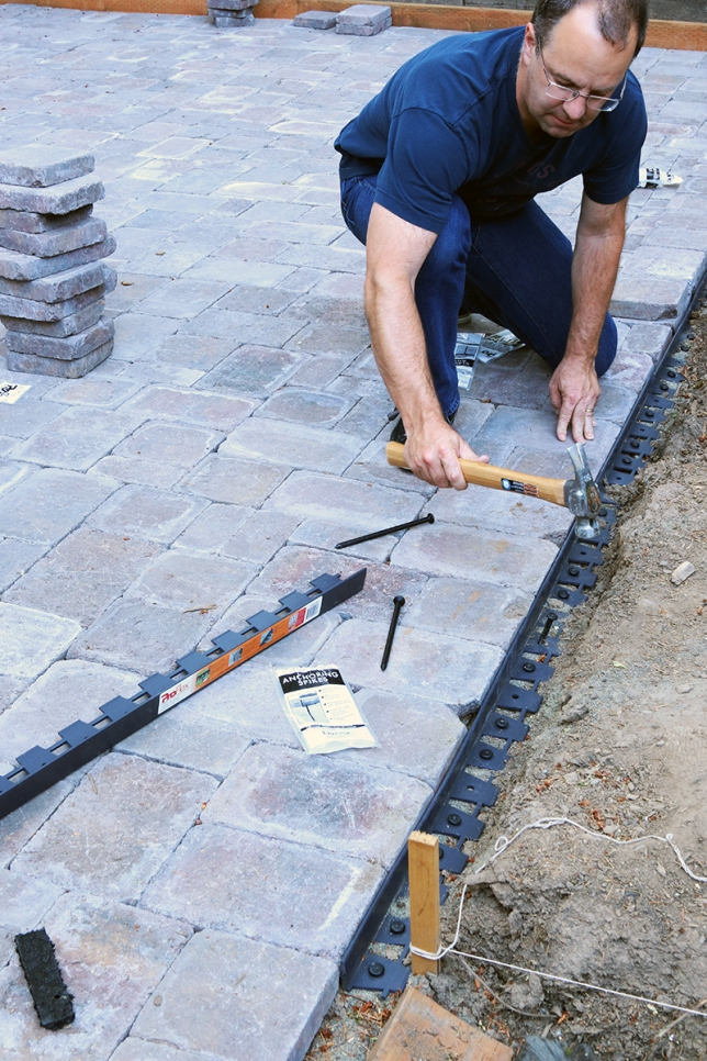 You need to put down edging wherever the pavers could drift outward. Long plastic spikes hold it in place.